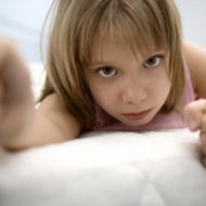 девочка держится за решетку кровати
