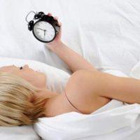 девушка лежит с будильником в руках